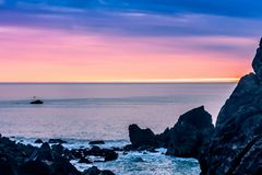 Magenta Sunset over the Pacific Ocean. Soft sunset framed by large rocks in the Pacific Ocean Royalty Free Stock Photos