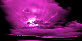 Magenta Sunset with Suns Rays. Through cumulonimbus and nimbostratus cloud from Styles Point, Lake Macquarie. New South Wales. Showing Clearly defined stock photography