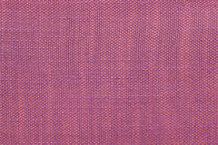 Magenta textile background with checkered pattern, closeup. Structure of the fabric macro. Royalty Free Stock Image