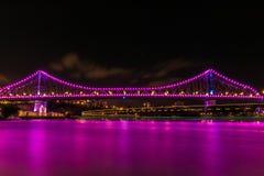 Magenta water under bridge at night. River water of magenta color flowing under modern illuminated bridge at dark night in Brisbane, Australia stock photography
