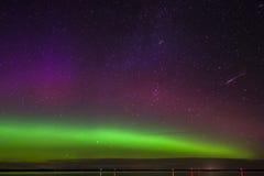Magentafärgad och purpurfärgad norrsken för gräsplan, med meteor över en sjö i North Dakota royaltyfria bilder