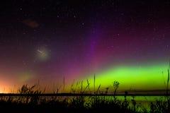 Magentafärgad och purpurfärgad norrsken för gräsplan, med meteor Royaltyfria Bilder