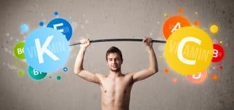 Mager grabb som lyfter färgrika vitaminvikter Arkivbilder
