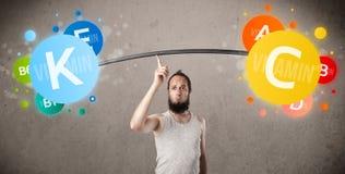 Mager grabb som lyfter färgrika vitaminvikter Fotografering för Bildbyråer