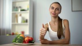 Mager meisje die duimen tonen die, groenten, gezondheid, juiste voeding adviseren stock foto