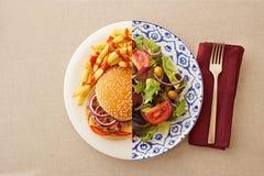 Mager sallad mot den fetthaltiga hamburgaren royaltyfri bild