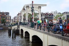 Magere Brug, Amsterdam. AMSTERDAM, NETHERLANDS - JULY 8, 2017: People visit Magere Brug (The Skinny Bridge) in Amsterdam, Netherlands. Amsterdam is the capital royalty free stock photo
