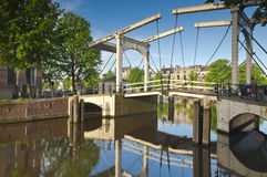 Magere Brug, Amsterdam. Iconic Magere Brug (1671) delicate wooden bridge reflected in the Amstel canal Amsterdam stock image