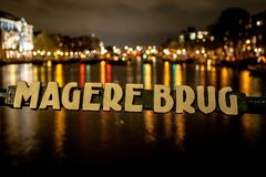 Magere Brug in Amsterdam at night. The Magere Brug Skinny Bridge is a bridge over the river Amstel in the city centre of Amsterdam. It connects the banks of the royalty free stock image