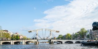 Magere Brug, Skinny Bridge on the Amstel River. AMSTERDAM, HOLLAND - AUGUST 17, 2017; small vintage private VIP canal cruise boat passes through while people royalty free stock images