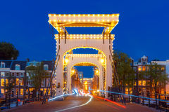 Magere Brug, Skinny bridge, Amsterdam, Netherlands. Magere Brug, Skinny bridge, with night lighting over the river Amstel in the city centre of Amsterdam royalty free stock images