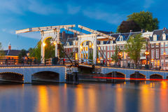 Magere Brug, Skinny bridge, Amsterdam, Netherlands. Magere Brug, Skinny bridge, with night lighting over the river Amstel in the city centre of Amsterdam royalty free stock photos