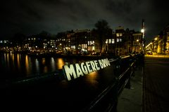 Magere Brug in Amsterdam at night. The Magere Brug Skinny Bridge is a bridge over the river Amstel in the city centre of Amsterdam. It connects the banks of the stock photo