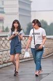 Magere en vette Chinese meisjes op een voetbrug, Peking, China Royalty-vrije Stock Foto