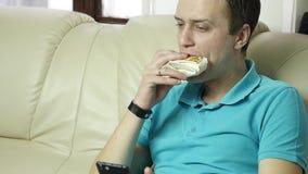 Magere mens die ongezonde kost met groot plezier eten de kerel eet snel voedselsnack Langzame Motie stock footage
