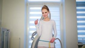 Magere slanke vrouw die haar taillevolume met lint meten stock videobeelden