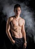 Magerer athletischer hemdloser junger Mann, der auf dunklem Hintergrund steht Lizenzfreies Stockbild