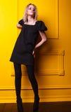 Mageres Mädchen, das auf gelbem Hintergrund aufwirft Stockbilder