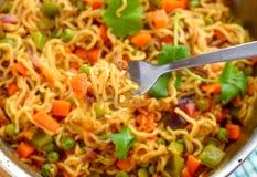 Magginoedels met groenten worden gekookt die stock fotografie