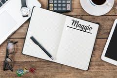 Maggio-Italiener-Mai-Monatsname auf Papiernotizblock am Schreibtisch Stockfotos