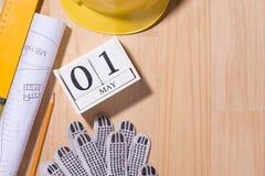 1° maggio l'immagine di può 1 calendario di legno dei blocchetti di bianco con gli strumenti della costruzione sulla tavola Immagini Stock