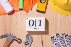 1° maggio l'immagine di può 1 calendario di legno dei blocchetti di bianco con gli strumenti della costruzione sulla tavola Immagine Stock