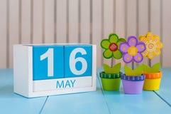16 maggio L'immagine di può calendario di legno di colore 16 su fondo bianco con i fiori Giorno di primavera, spazio vuoto per te Fotografia Stock