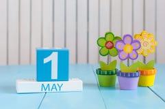 1° maggio l'immagine di può 1 calendario di legno di colore su fondo bianco con i fiori Giorno di primavera, spazio vuoto per tes Immagini Stock