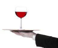 Maggiordomo con il vetro del vino rosso sul cassetto fotografia stock libera da diritti