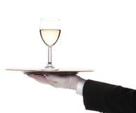 Maggiordomo con il vetro di vino bianco sul cassetto fotografia stock libera da diritti