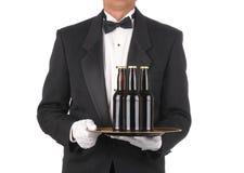 Maggiordomo con le bottiglie da birra sul cassetto immagini stock