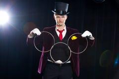 Magi kapacitet, cirkus, showbegrepp - trollkarlen i visningtrick för bästa hatt med att anknyta ringer royaltyfri foto