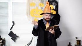 Magia, periodo, libro di magia Il mago barbuto legge un vecchio libro su magia Stregone di Halloween Il mago legge un segreto stock footage