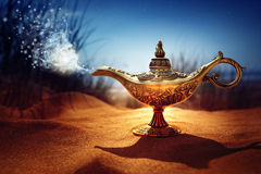 Magic Aladdins Genie lamp. Magic lamp in the desert from the story of Aladdin with Genie appearing in blue smoke concept for wishing, luck and magic stock photography