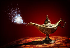 Magic Aladdins Genie lamp. Magic lamp from the story of Aladdin with Genie appearing in blue smoke concept for wishing, luck and magic royalty free stock photography