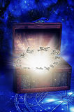 Magic astrology. An old box with glowing shine and symbols of zodiac signs over starry Universe and blue horoscope like a concept for magic astrology Stock Image