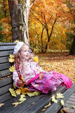 Magic autumn. A little girl sitting drawn in feet on a bench in autumn park, holding in her hand twigs of barberry and looking with admiration at the Royalty Free Stock Photography