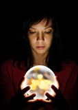 Magic ball. Girl holds in its hands ball of light Royalty Free Stock Photography