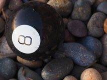 Magic 8 Ball Washed Up on Shore. A Magic 8 ball resting on rocks after being washed up on shore in Encinitas, California stock images