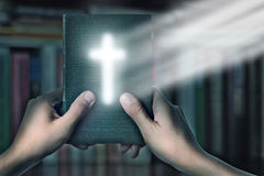 Magic Bible book with magic cross light. In hand against the shelves with books, search for information in an Bible, a reading room in the library and study royalty free stock photo
