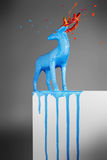 Magic blue deer melting on a white pedestal Royalty Free Stock Photos
