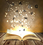 Magic book. Open on the wooden table Stock Images
