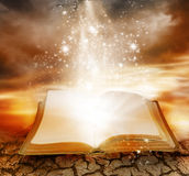 Magic book. A golden book of knowledge lies open with stars rising from the covers and lifting the book from the cracked surface. Golden cloudy sky serves as a