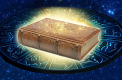 Magic book. A magic astrological book lying on blue zodiac with mystical ligthning Royalty Free Stock Photos