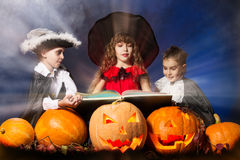 Magic book. Cheerful children in halloween costumes standing with pumpkins and a book of spells. Over dark background Stock Image