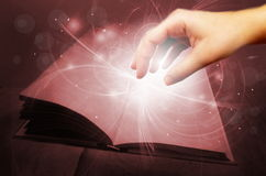 Magic book with hand. Photo manipulation of open magic book with white lights and human hand royalty free illustration