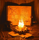 Satanic rites 2 (shadows). Magic book with mystic symbols and black skull with candles Royalty Free Stock Image