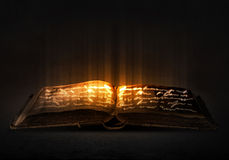 Magic book. Old black magic book with lights on pages Royalty Free Stock Photos