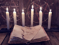 Magic book with pentagram and evil candles for occult ritual. Halloween background, black magic rite or spell, occult and esoteric objects on witch table stock image