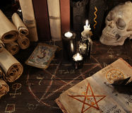 Magic book with pentagram, the tarot cards and candles on wooden planks. Magic book with pentagram, the tarot cards, warlock books, skull and black candles on royalty free stock photography